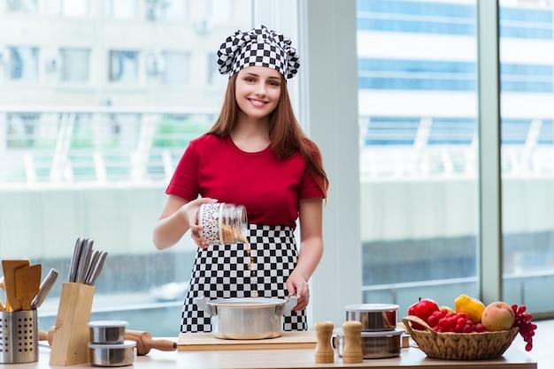 Junge hausfrau, die suppe in der küche zubereitet