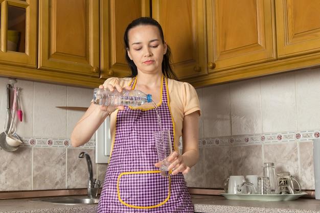 Junge hausfrau, die wasser in das glas gießt