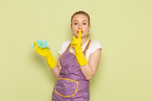 Junge hausfrau im hemd und im farbigen umhang, der gelbe handschuhe trägt, die schweigenzeichen auf grün zeigen