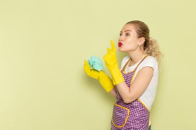 Junge hausfrau im hemd und im farbigen umhang, der gelbe handschuhe trägt und auf grün aufwirft