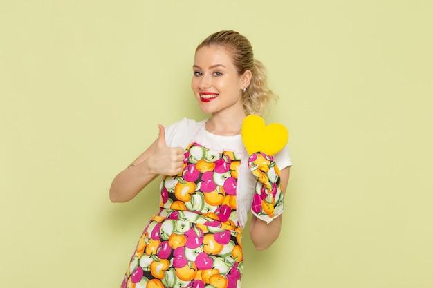Junge hausfrau im hemd und im farbigen umhang, der gelbe herzform auf grün hält