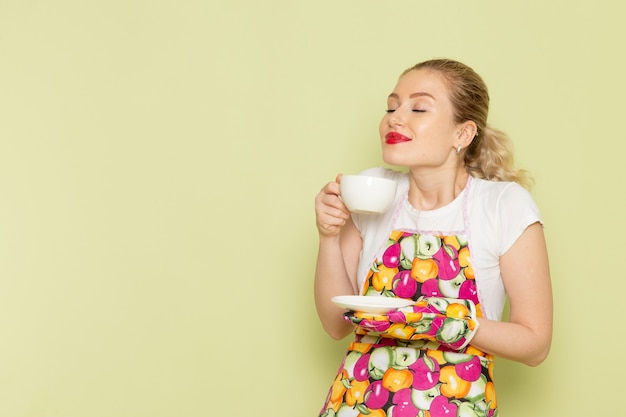 Junge hausfrau im hemd und im farbigen umhang, der mit tasse tee auf grün aufwirft