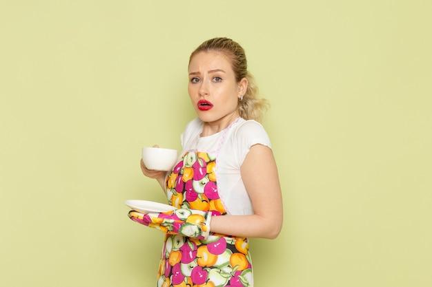 Junge hausfrau im hemd und im farbigen umhang, der tasse tee auf grün hält