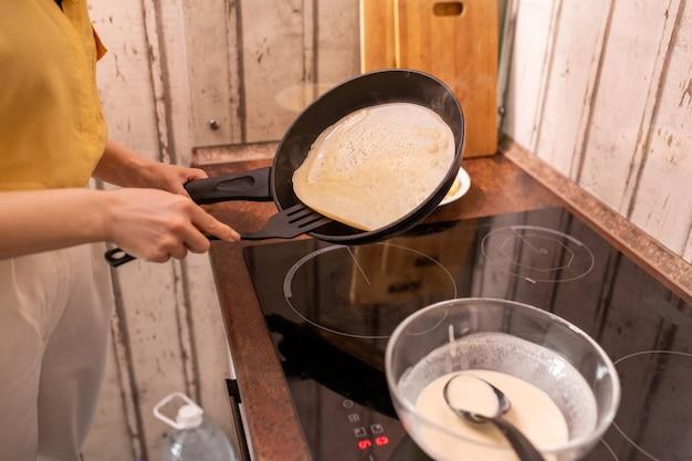 Junge hausfrau in der freizeitkleidung, die bratpfanne über elektroherd hält, während leckere pfannkuchen zum frühstück am morgen kocht