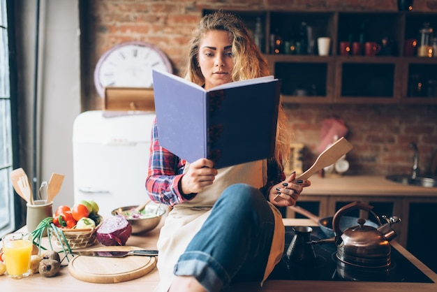 Junge hausfrau in einer schürze liest rezeptbuch