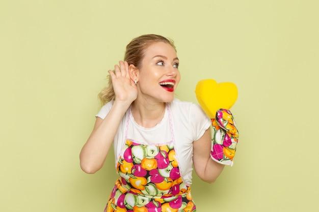 Junge hausfrau in hemd und buntem umhang, der gelbes herzzeichen auf grün lächelt und hält