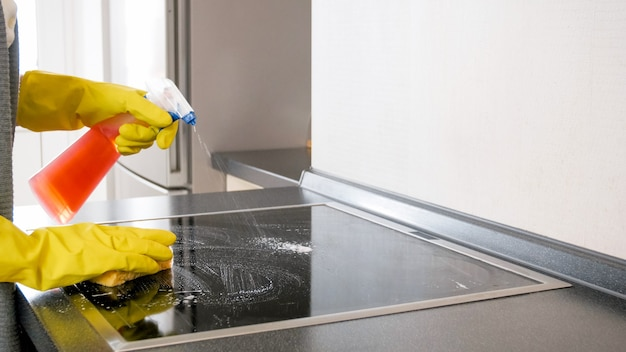 Junge hausfrau mit chemischem spray beim reinigen des elektroherds in der küche.