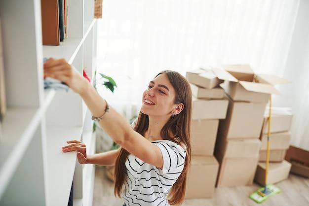 Junge hausfrau putzt neue wohnungen. machen sie sich bereit, die kartons mit gegenständen auszupacken.