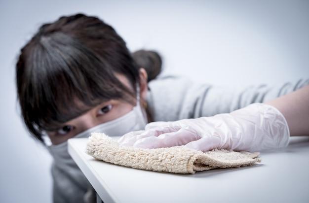 Junge hausfrau putzt, wischt die tischoberfläche ab, um die ausbreitung der infektion mit nassem lappen zu stoppen, antibakteriell, nahaufnahme, lebensstil.