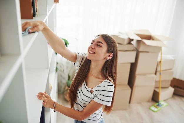 Junge hausfrau reinigt neue wohnungen. bereiten sie sich darauf vor, die kartons mit gegenständen auszupacken.