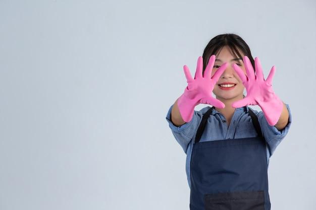 Junge hausfrau trägt gelbe handschuhe beim putzen mit dem produkt von sauber auf weißer wand.