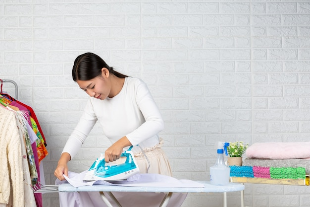 Junge hausfrauen, die bügeleisen benutzen, die seine kleidung auf einem weißen ziegelstein bügeln.