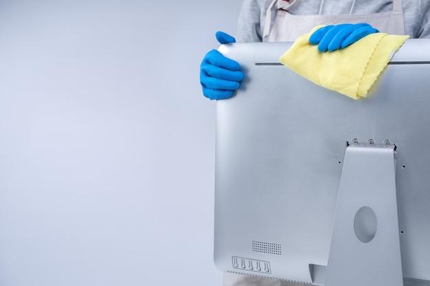 Junge haushälterin in schürze reinigt silberne computeroberfläche mit blauen handschuhen, nassem gelbem lappen, nahaufnahme, kopienraum, leeres designkonzept.
