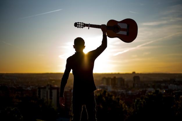 Junge hebt die gitarre in der stadt von madrid, spanien im hintergrund auf.
