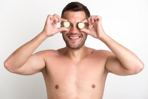Junge hemdlose lächelnde mannbedeckungsaugen mit der gurkenscheibe, die gegen weiße wand steht
