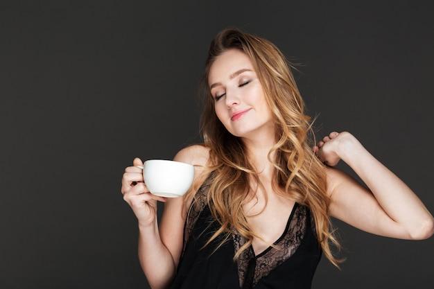 Junge herrliche frau, die kaffee trinkt und aufwirft