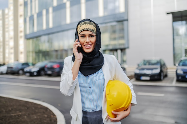 Junge herrliche lächelnde attraktive weibliche muslimische architektin, die vor firmengebäude mit helm unter achsel steht und gespräch mit konstrukteur hat.