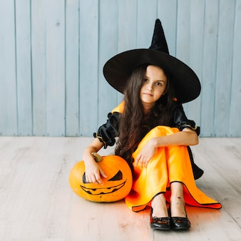 Junge hexe, die mit kürbis auf halloween-partei sitzt