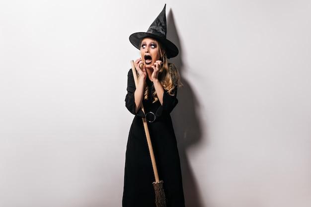 Junge hexe im hut, der in halloween mit unheimlichem gesichtsausdruck aufwirft. innenfoto des schockierten blonden weiblichen modells im zaubererkostüm.