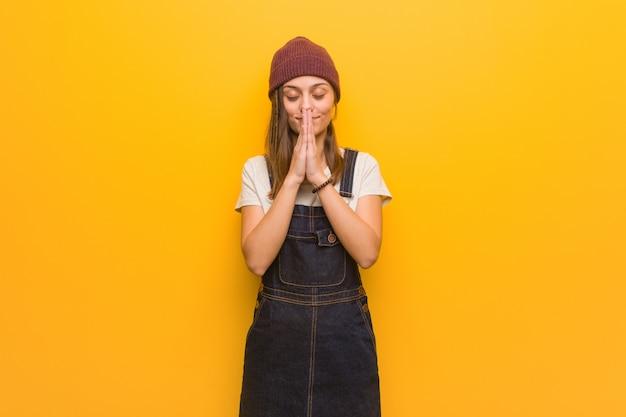 Junge hippie-frau, die sehr glücklich und überzeugt betet