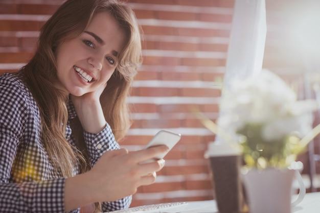 Junge hippie-geschäftsfrau, die ihr telefon an ihrem schreibtisch im büro verwendet