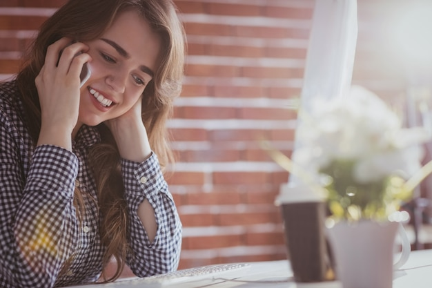 Junge hippie-geschäftsfrau, die mit ihrem telefon an ihrem schreibtisch im büro nennt