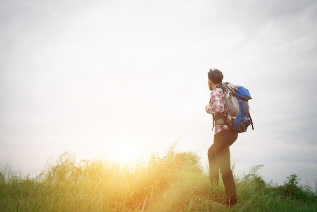 Junge hippie-mann im freien mit rucksack auf der schulter, zeit zu