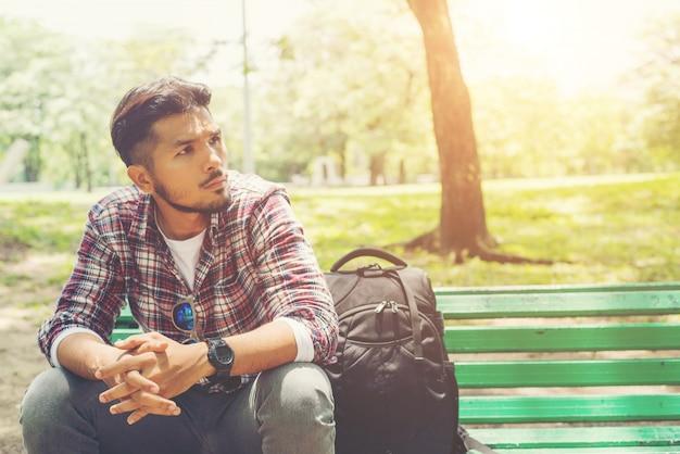 Junge hippie-mann mit rucksack auf einer holzbank neben sitzen