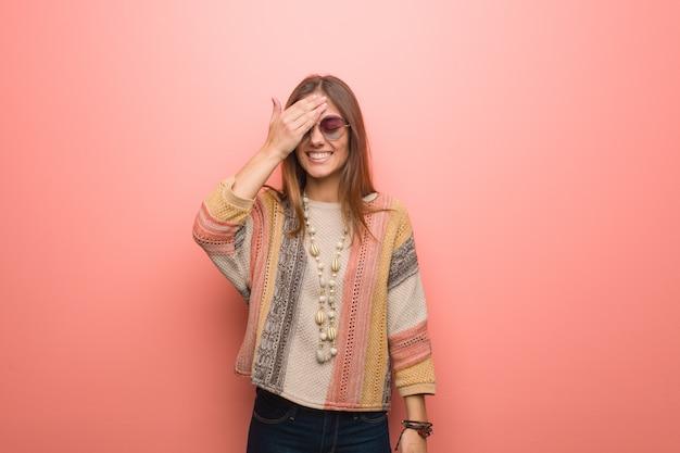 Junge hippiefrau auf dem rosa vergesslichen hintergrund, verwirklichen etwas