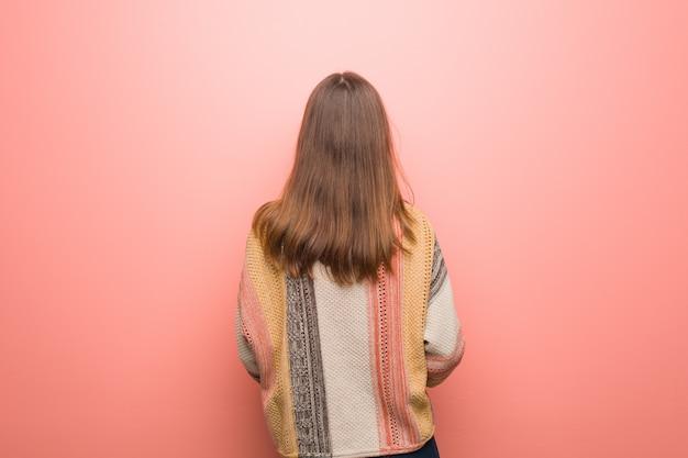 Junge hippiefrau auf dem rosa von hinten, zurück schauend