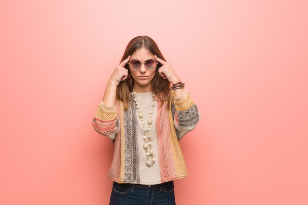 Junge hippiefrau auf rosa handelnkonzentrationsgeste