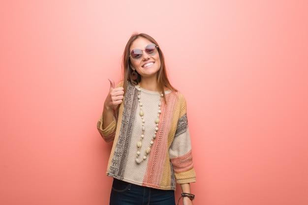 Junge hippiefrau auf rosa hintergrund oben lächelnd und daumen anhebend