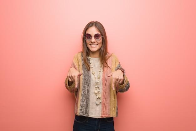 Junge hippiefrau, die auf die unterseite mit den fingern zeigt