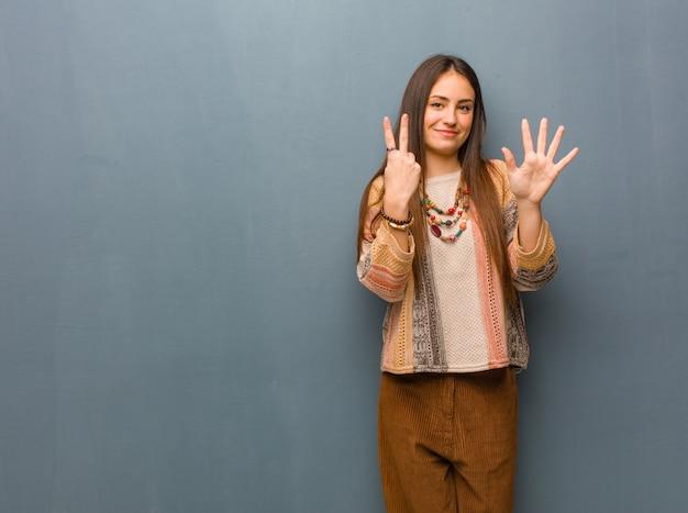 Junge hippiefrau, die nr. sieben zeigt