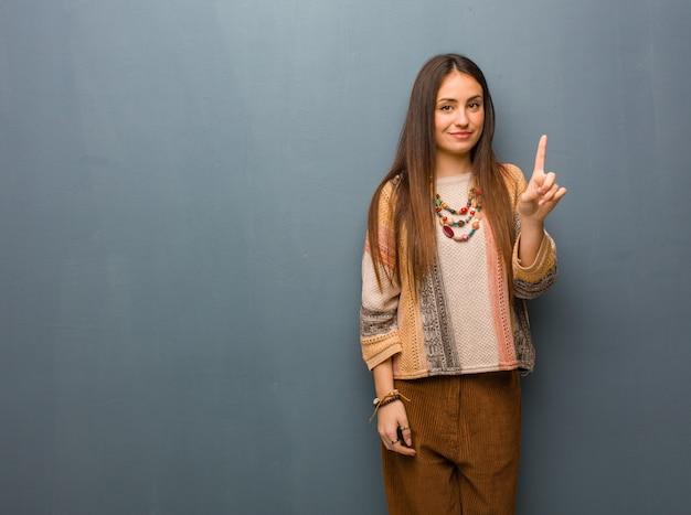 Junge hippiefrau, die nummer eins zeigt