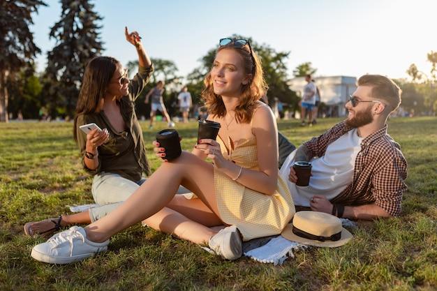 Junge hipster-firma von freunden, die gemeinsam spaß im park haben und lächeln, musik auf kleinen drahtlosen lautsprechern hören?