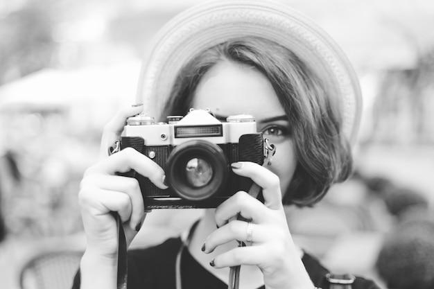 Junge hipster-frau, die eine retro-kamera in ihren händen hält und ein foto macht