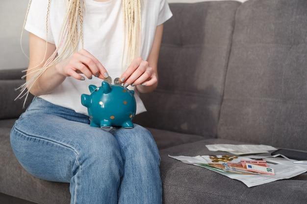 Junge hipster-frau, die münzen in sparbüchse für reisen setzt, die auf sofa zu hause sitzen. einsparungskonzept