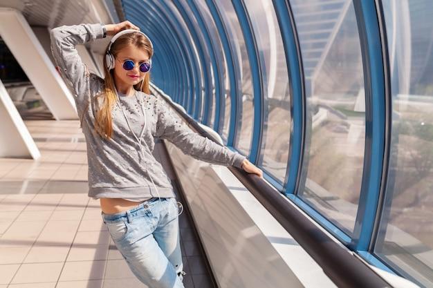Junge hipster-frau, die spaß im städtischen modernen gebäude tanzt, gekleidet in lässigem outfit, das musik in kopfhörern hört, jeans, pullover und sonnenbrille tragend