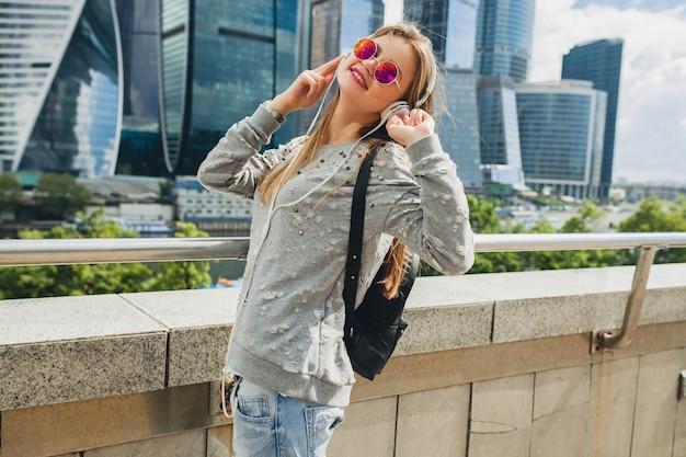 Junge hipster-frau, die spaß in der straße hat, die musik auf kopfhörern hört, rosa sonnenbrille tragend