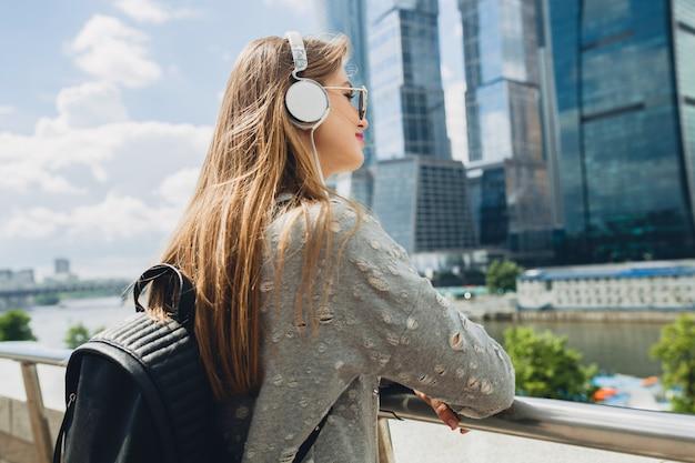 Junge hipster-frau, die spaß in der straße hat, die musik auf kopfhörern hört, rosa sonnenbrille und rucksack tragend, frühlingssommer-stadtstil