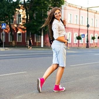 Junge hipster-frau, die verrückt wird und spaß in der innenstadt von europa hat, allein geht und reist, freude, gefühle, lässige stilvolle kleidung und rucksack, sonnige warme helle farben