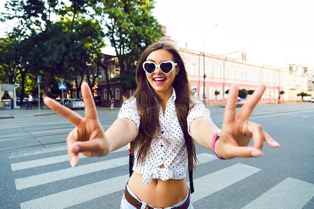 Junge hipster-frau, die verrückt wird und spaß in der innenstadt von europa hat, allein spazieren geht und reist, freude, emotionen, lässige stilvolle kleidung und rucksack,