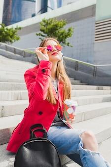 Junge hipster-frau im rosa mantel, jeans, die in der straße mit rucksack und kaffee sitzen musik auf kopfhörern hören