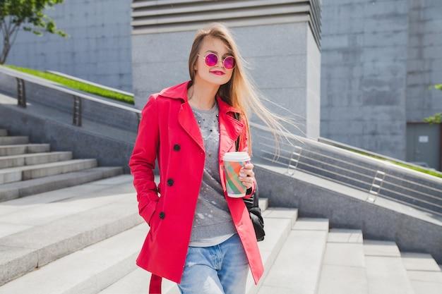 Junge hipster-frau im rosa mantel, jeans in der straße mit kaffee, der musik auf kopfhörern hört