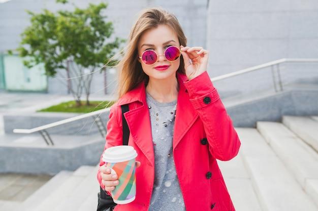 Junge hipster-frau im rosa mantel, jeans in der straße mit rucksack und kaffee, die musik auf kopfhörern hören, sonnenbrille tragend