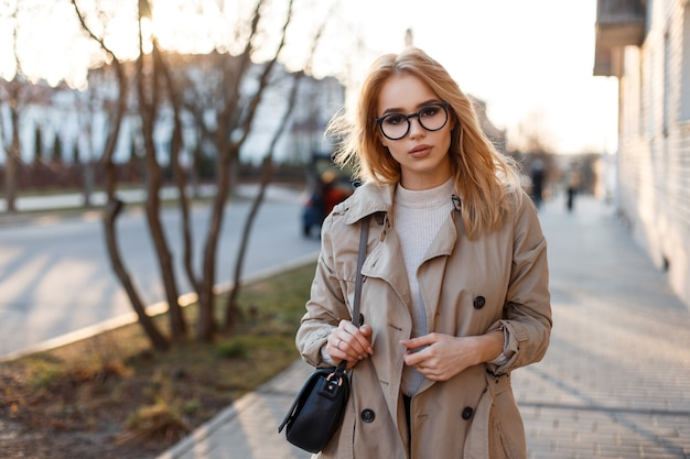 Junge hipster-frau in einem stilvollen frühlingsmantel in modischen gläsern in einem weißen t-shirt in einer schwarzen lederhandtasche, die entlang der straße auf vintage-gebäuden geht. europäisches mädchen.