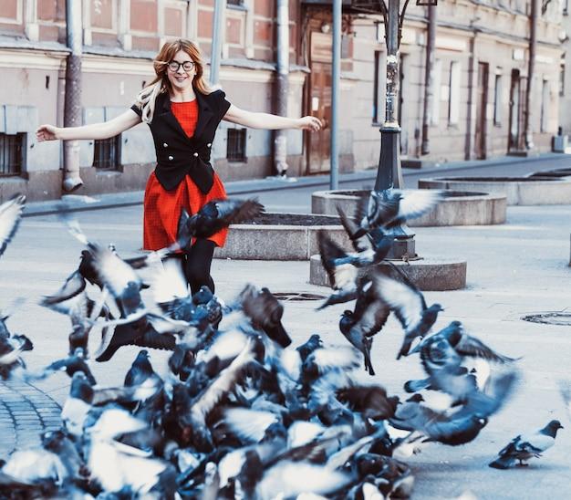 Junge hipster-frau mit rotem kleid in der stadt. frühling und vögel tauben.