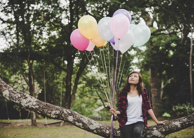 Junge hipster frau sitzt auf baum zweig mit bunten ballons in der hand, entspannung genießen urlaub.