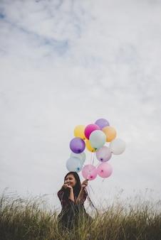 Junge hipster frau sitzt mit bunten luftballons im feld, blauer himmel hintergrund.